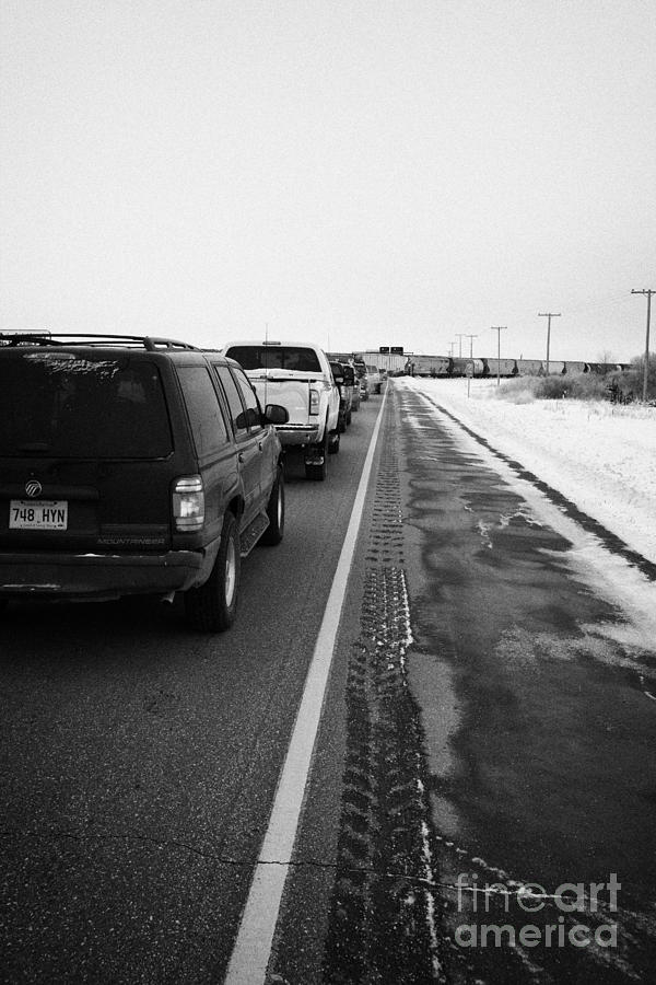 cars waiting on train crossing trans-canada highway in winter outside Yorkton Saskatchewan Canada Photograph  - cars waiting on train crossing trans-canada highway in winter outside Yorkton Saskatchewan Canada Fine Art Print