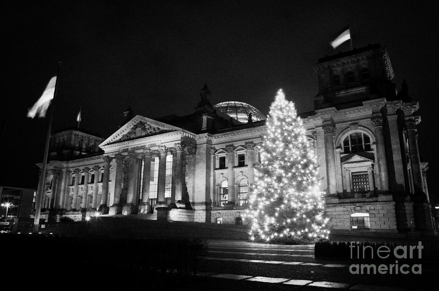 christmas tree and german flag flying fluttering on flagpole outside reichstag building Berlin Germany Photograph
