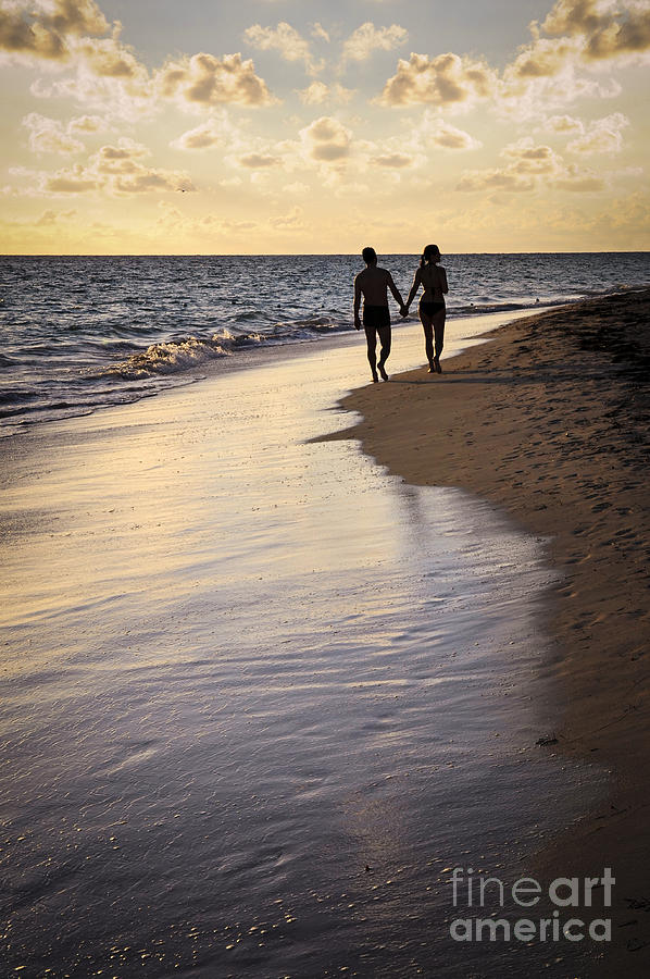 Couple Walking On A Beach Photograph