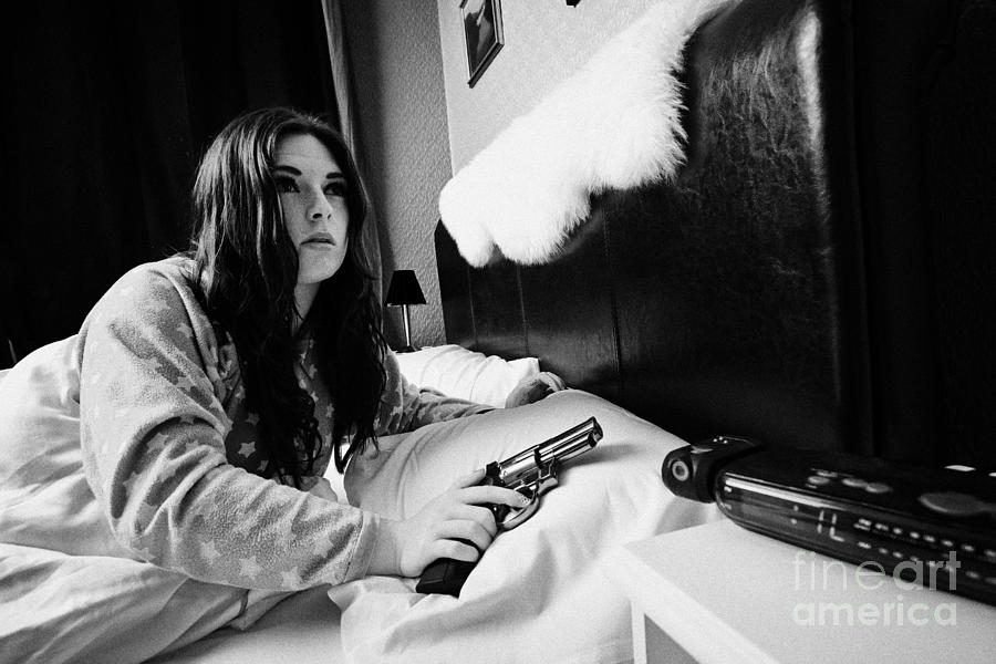 Early Twenties Woman Waking Holding Handgun In Bed In A Bedroom Photograph