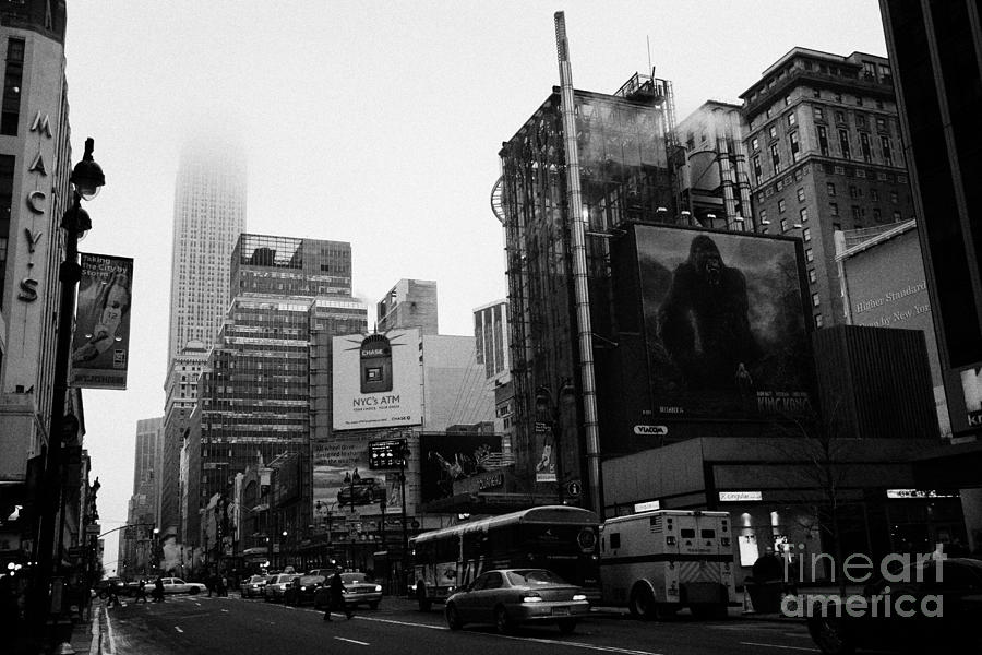 empire state building shrouded in mist from west 34th Street and 7th Avenue new york city usa Photograph