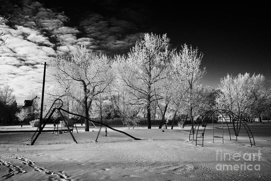 empty childrens playground with hoar frost covered trees on street in small rural village of Forget  Photograph