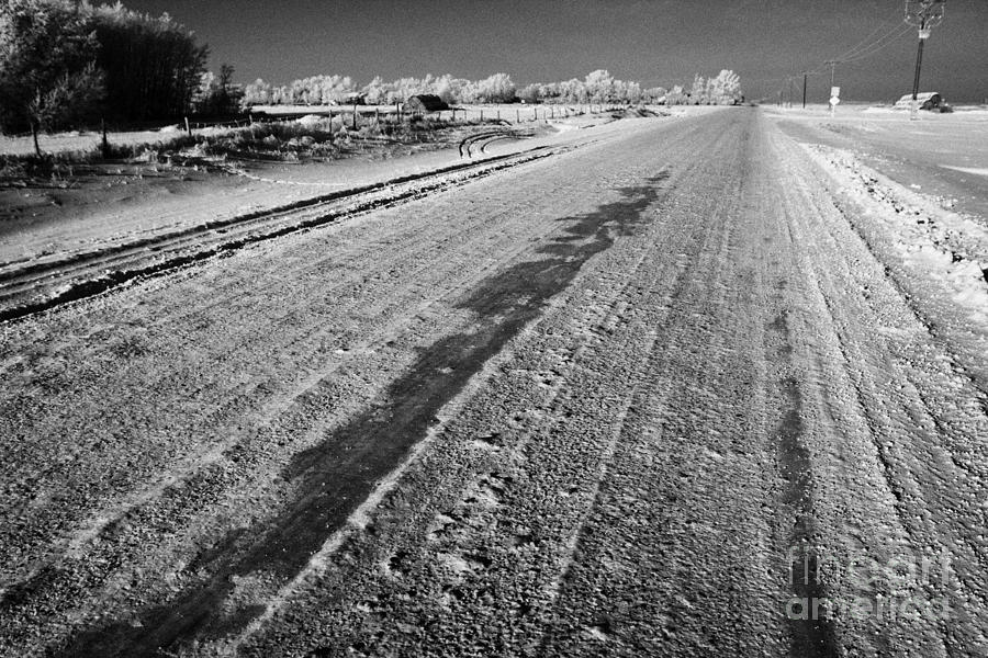 frozen salt and grit covered rural small road in Forget Saskatchewan Canada Photograph
