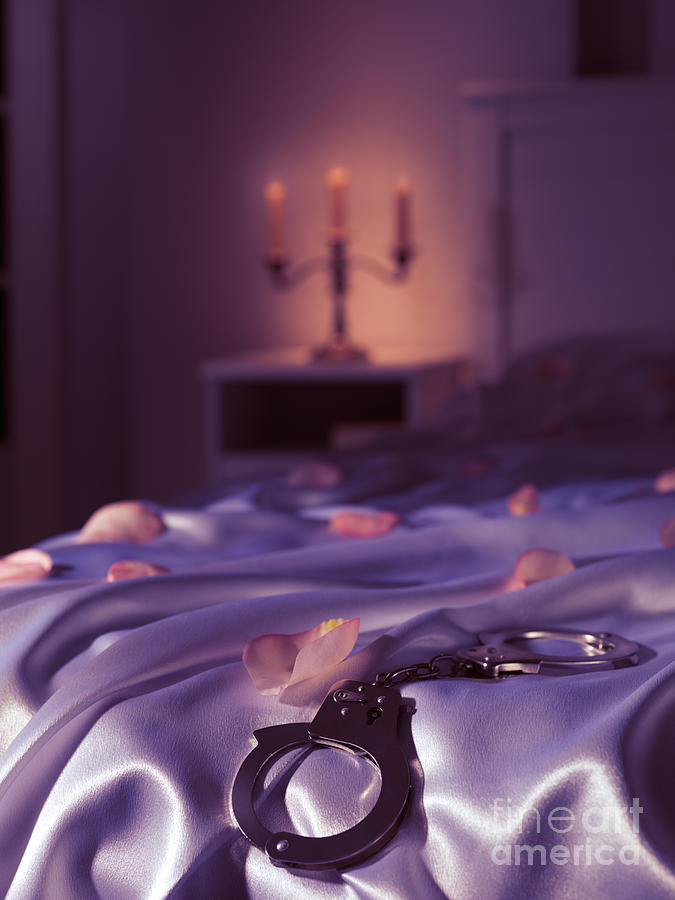 Handcuffs And Rose Petals On Bed Photograph