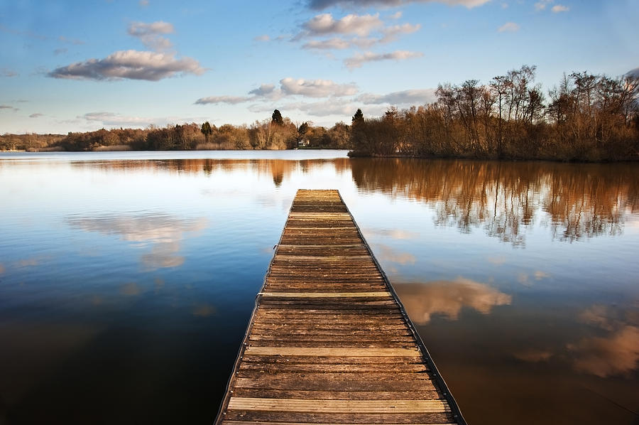 Pier Photograph - Landscape Of Fishing Jetty On Calm Lake At Sunset With Reflectio by Matthew Gibson