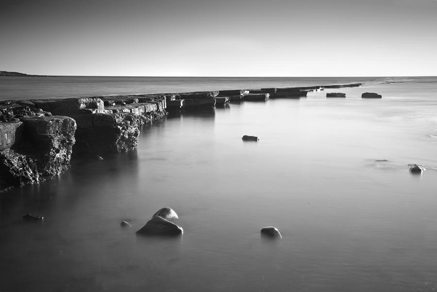 Long Exposure Image Of Tide Going Out Over Rock Ledge During Sun Photograph