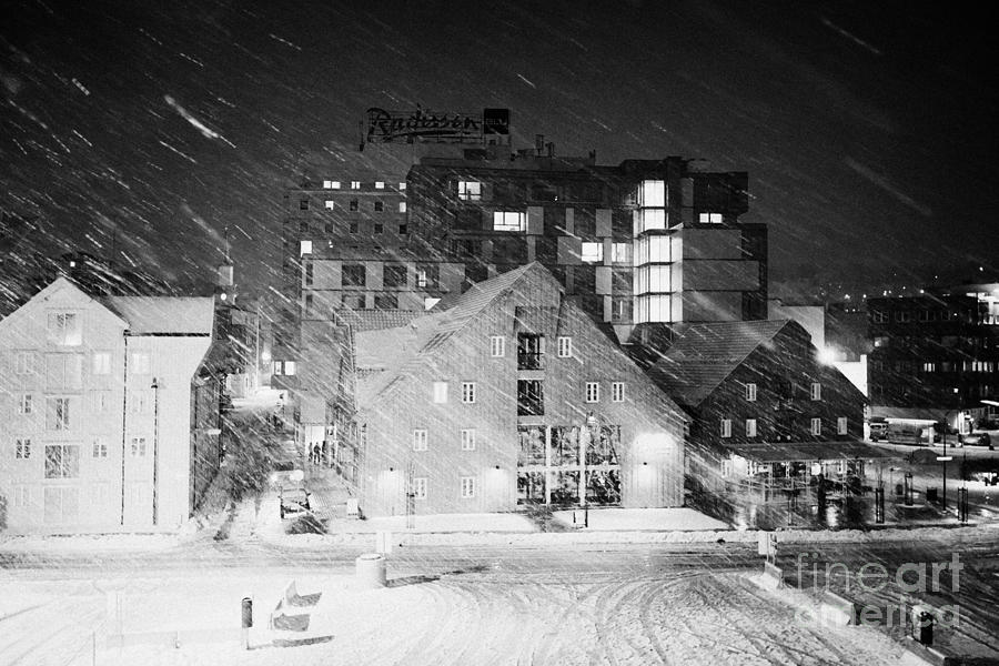 looking out atTromso bryggen quay harbour on a cold snowy winter night troms Norway europe Photograph