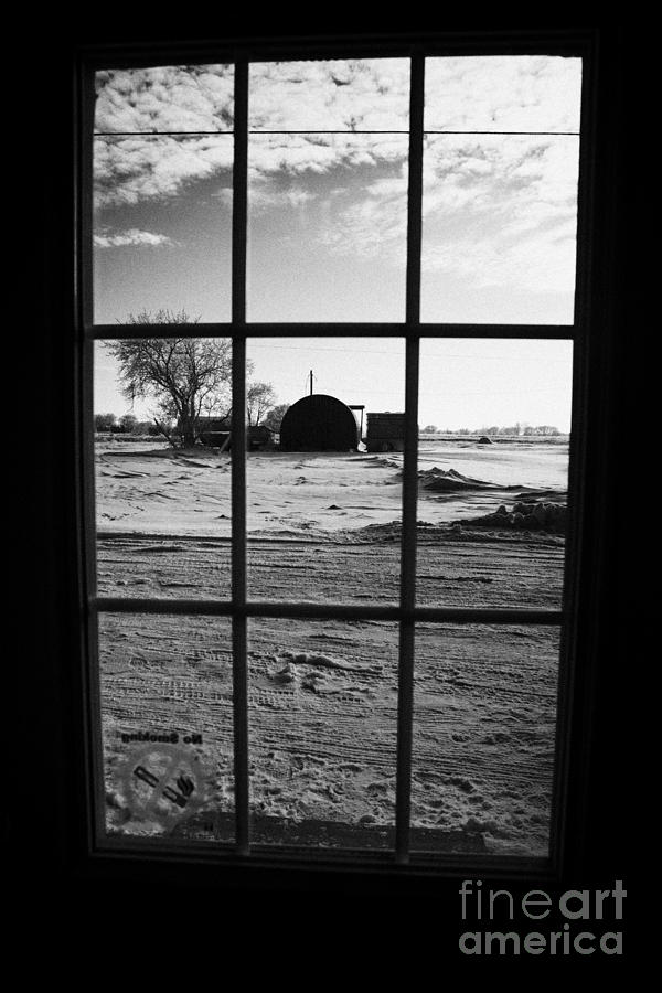 looking out through door window to snow covered scene in small rural village of Forget Photograph