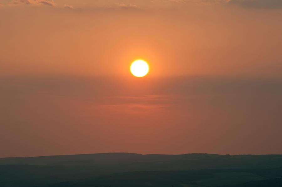 Low Setting Sun Over Distant Landscape Photograph