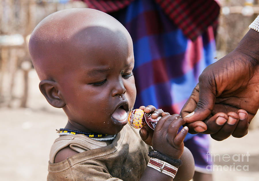 Maasai Child Trying To Eat A Lollipop In Tanzania Photograph