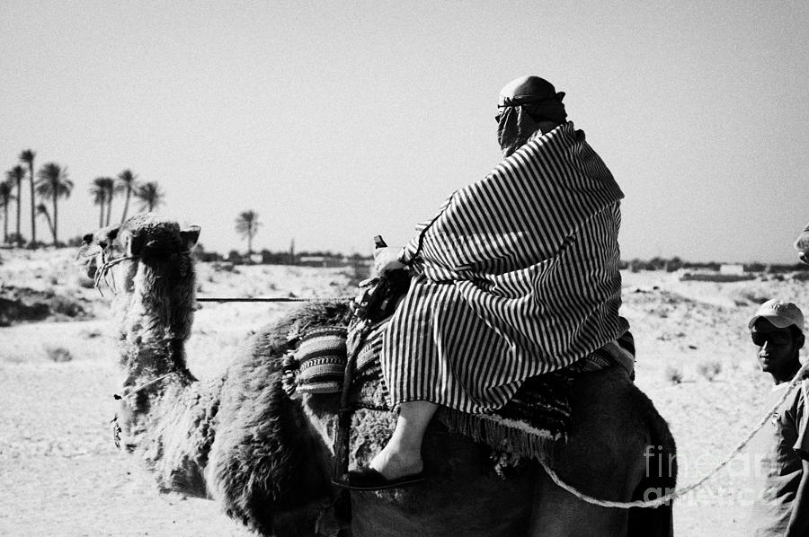 male tourist in desert clothing being led on the back of a camel into the sahara desert at Douz Tunisia Photograph