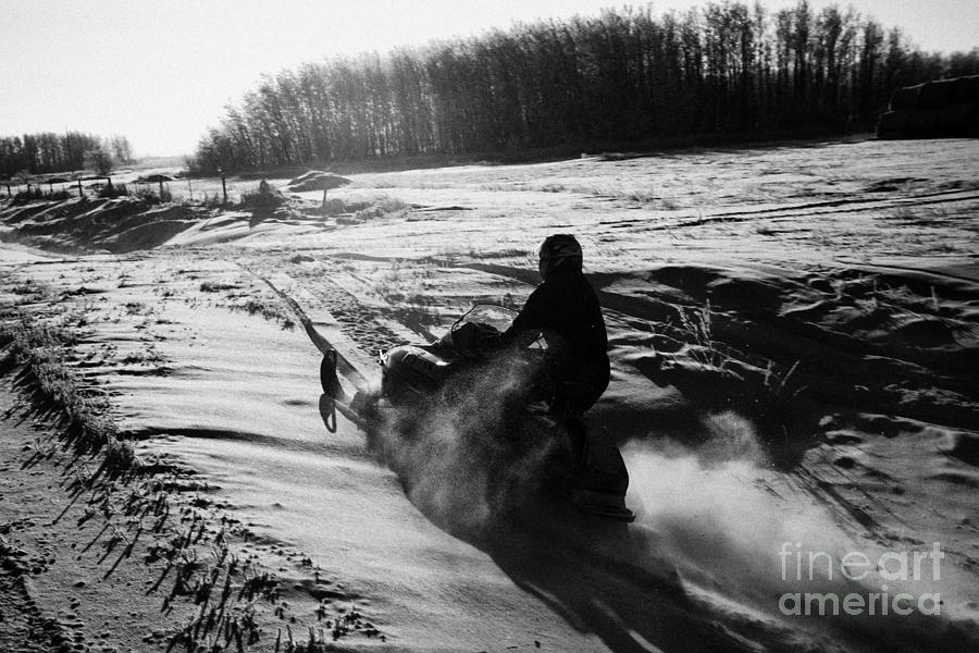 man on snowmobile crossing frozen fields in rural Forget canada Photograph  - man on snowmobile crossing frozen fields in rural Forget canada Fine Art Print