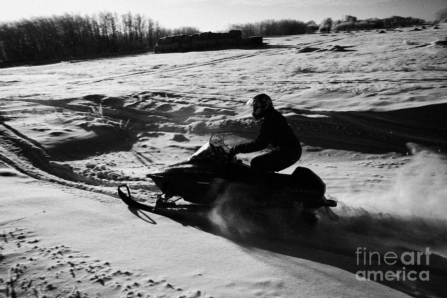 man on snowmobile crossing frozen fields in rural Forget Saskatchewan Photograph