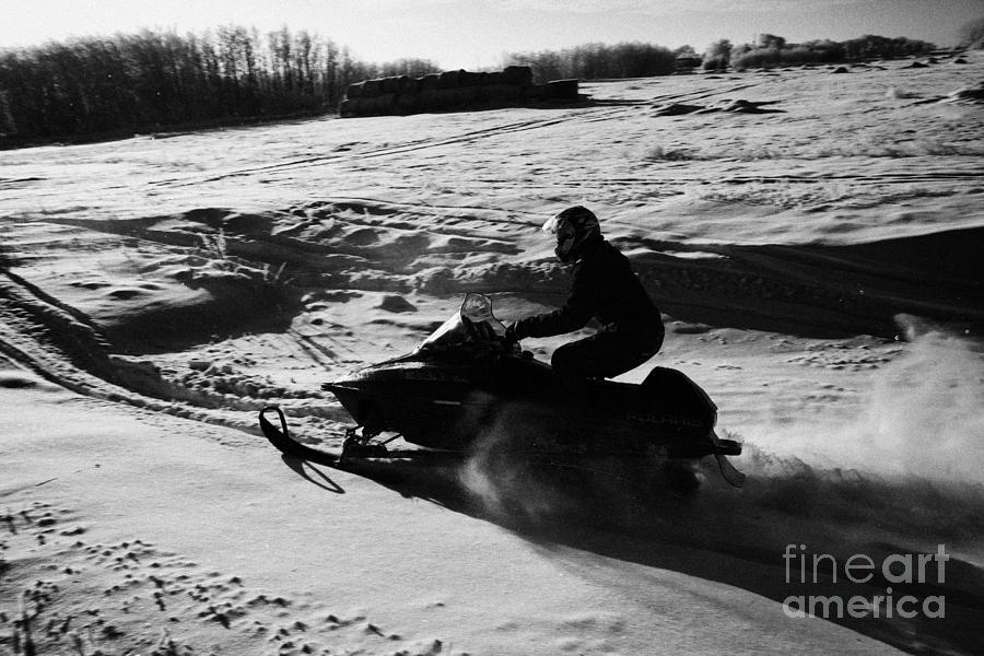 man on snowmobile crossing frozen fields in rural Forget Saskatchewan Photograph