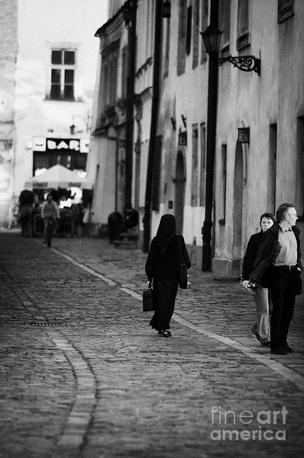 nun with briefcase walking up cobblestone street Kanonicza past tourists in old town krakow Photograph