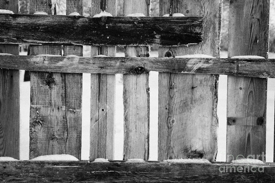 old patched up wooden fence using old bits of wood in snow Forget Photograph