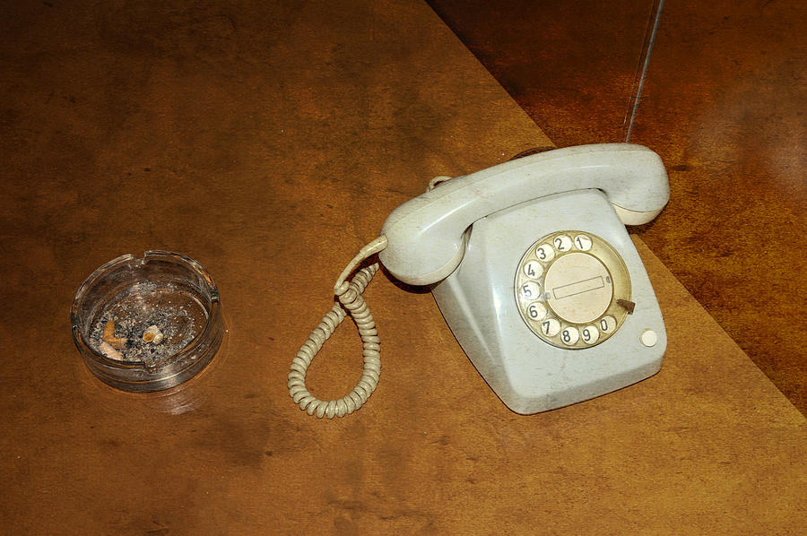 Old Telephone And Ashtray On Brown Table Photograph