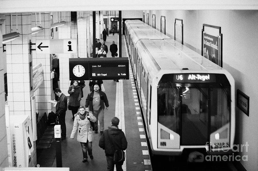 passengers on ubahn train platform as train leaves Friedrichstrasse u-bahn station Berlin Germany Photograph