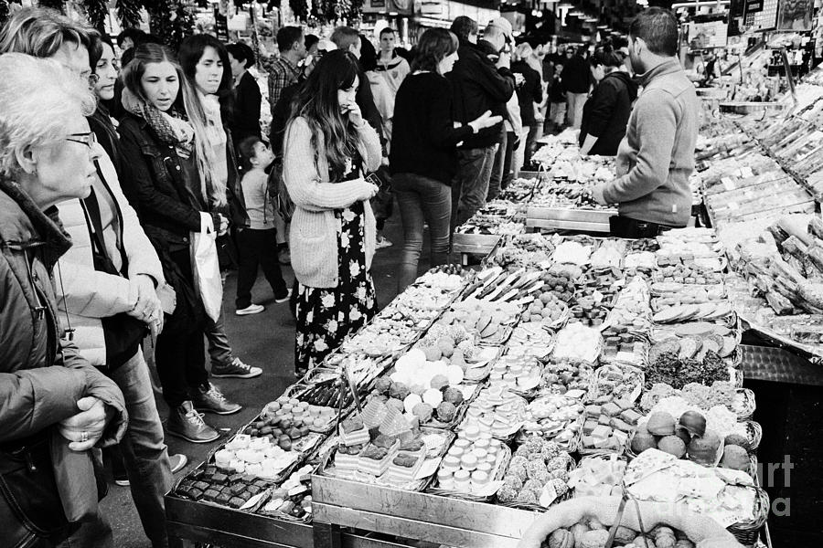 people buying chocolates on display inside the la boqueria market in Barcelona Catalonia Spain Photograph