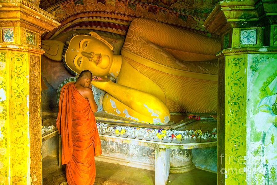 praying buddhist monk by a lying buddha in Sri Lanka ...