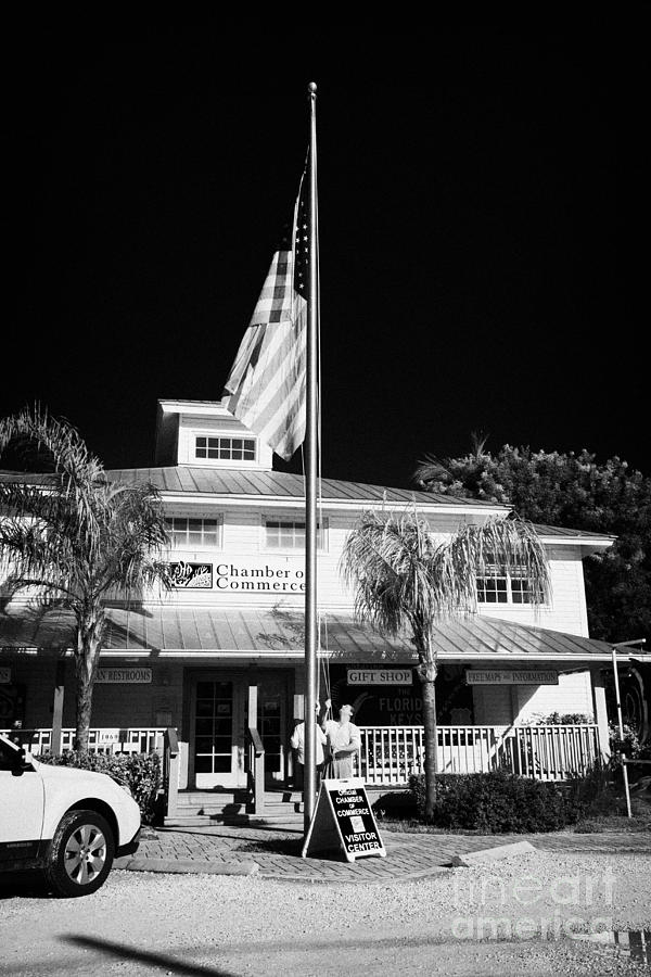 Raising The American Flag On A Flagpole Outside The Chamber Of Commerce Building In Key Largo Florid Photograph