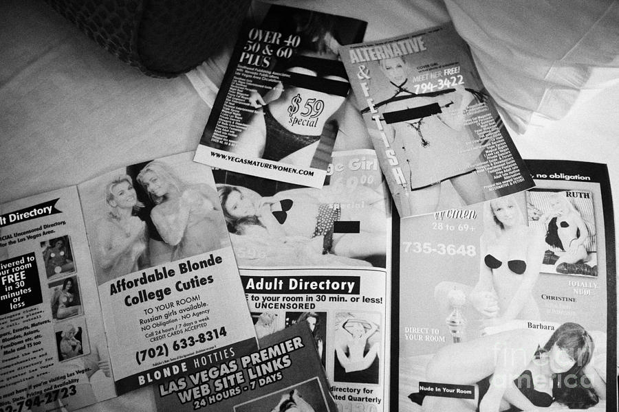 selection of leaflets advertising girls laid out on a hotel bed in Las Vegas Nevada USA Photograph