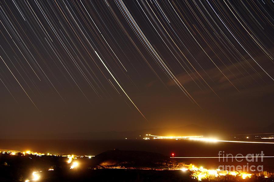Star Trails Above A Village Photograph