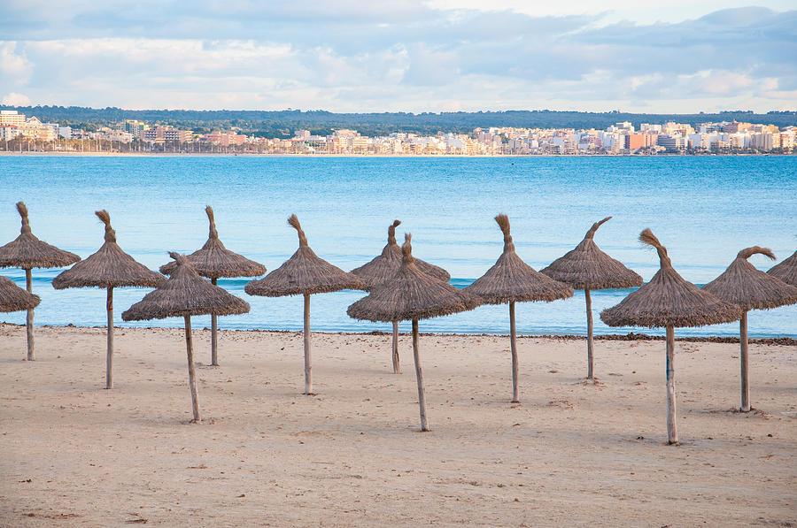 Straw Umbrellas On Empty Beach Photograph