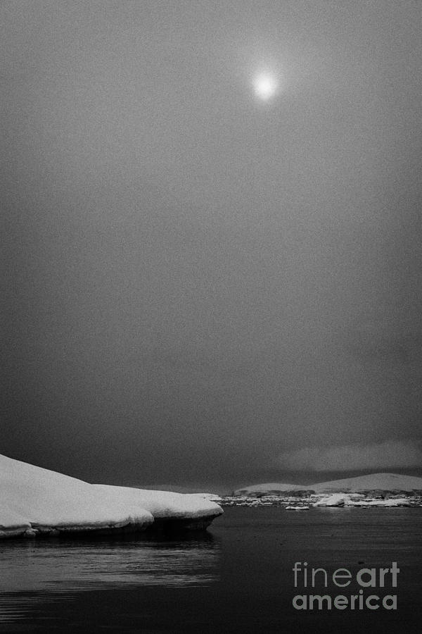 sun breaking through mist and cloud over snow covered ice shelf falling into the sea at Fournier Bay Photograph
