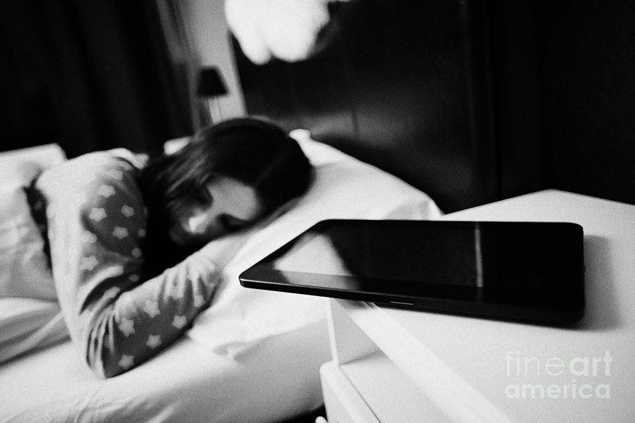 Tablet Computer On Bedside Table Of Early Twenties Woman In Bed In A Bedroom Photograph