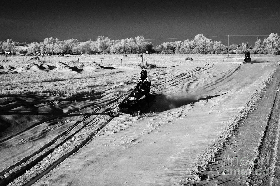 two men on snowmobiles crossing frozen fields in rural Forget Saskatchewan Canada Photograph  - two men on snowmobiles crossing frozen fields in rural Forget Saskatchewan Canada Fine Art Print