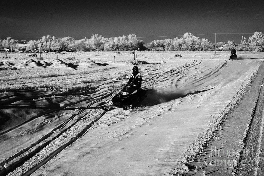 Man Photograph - two men on snowmobiles crossing frozen fields in rural Forget Saskatchewan Canada by Joe Fox