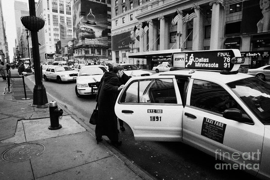 white middle aged passengers exit from yellow cab rear door at taxi rank on 7th Avenue Photograph