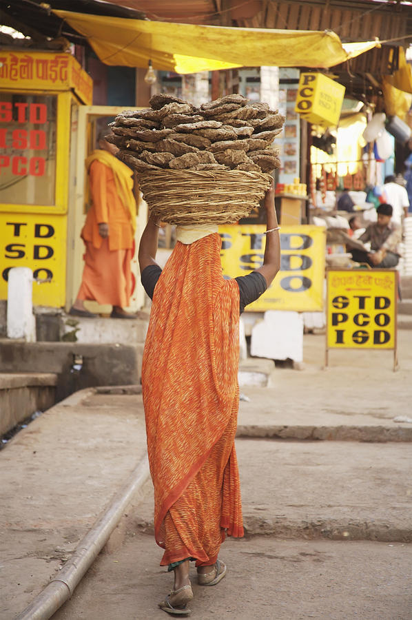 Woman Carrying Cow Dung In Basket On Photograph