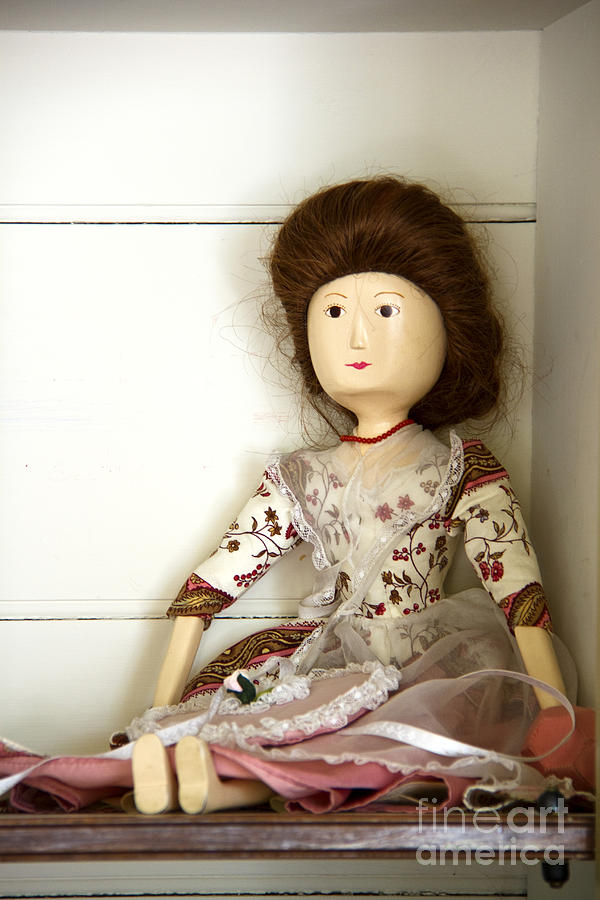Doll; Toy; Wood; Wooden; Painted; Hair; Gentry; Colonial; Caucasian; Sit; Sitting; Shelf; Pretty; Brunette; Beautiful; Feminine; Dress; Necklace; Stare; Staring; Tiny; Female; Woman; Lady; Store; Toy Room Photograph - Wooden Doll by Margie Hurwich