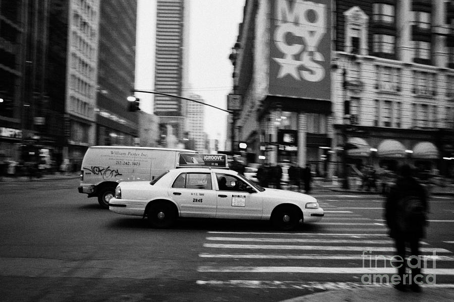 yellow cab taxi blurs past pedestrian waiting at crosswalk on Broadway outside macys new york usa Photograph