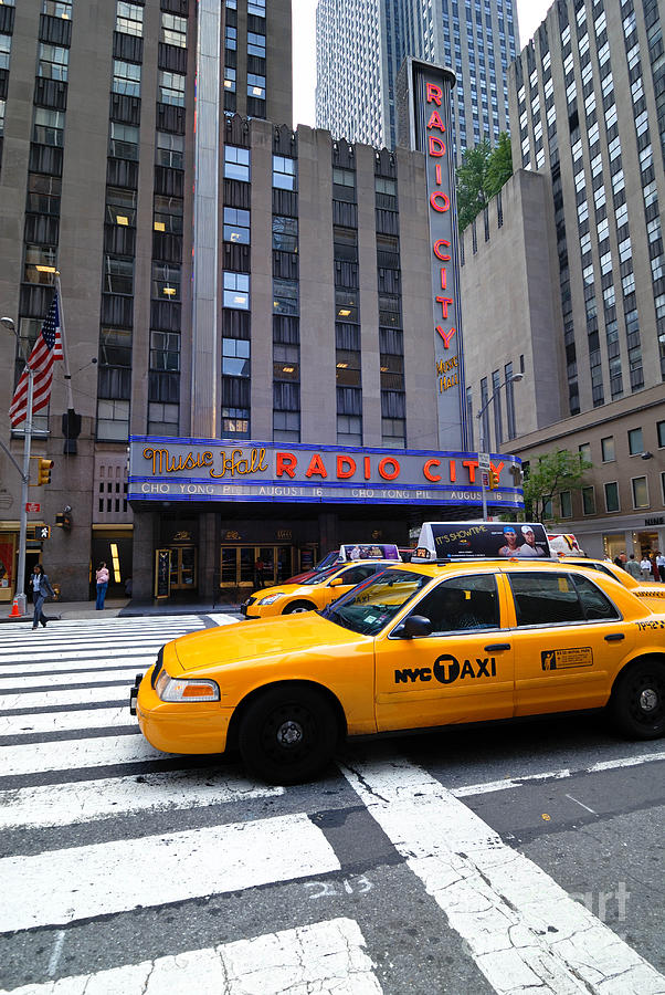 Yellow Cabs Pass In Front Of Radio City Music Hall Photograph  - Yellow Cabs Pass In Front Of Radio City Music Hall Fine Art Print