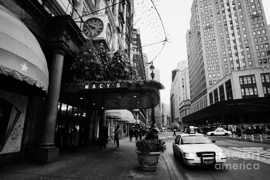 yellow taxi cab waits outside entrance to Macys department store on Broadway and 34th street Photograph