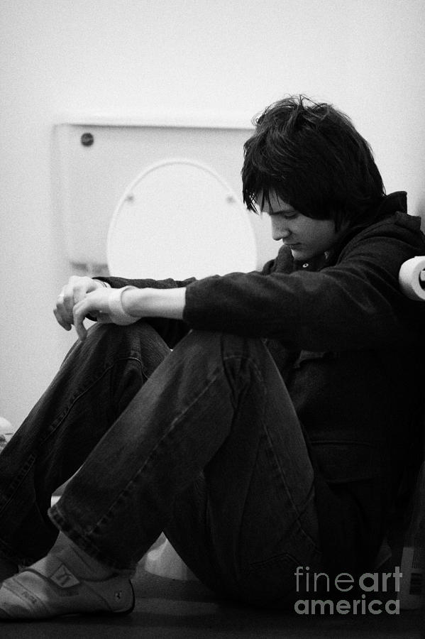 Young Dark Haired Teenage Man Sitting On The Floor Of The Bathroom With Back Against The Wall In The Photograph