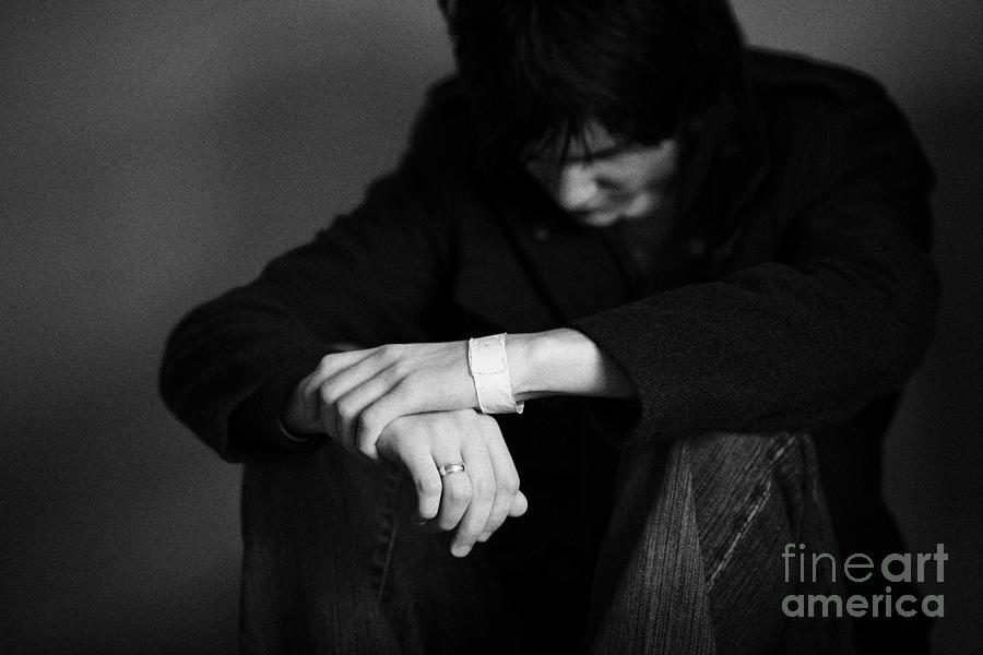 Young Dark Haired Teenage Man Sitting On The Floor With Back Against The Wall In The Fetal Position  Photograph