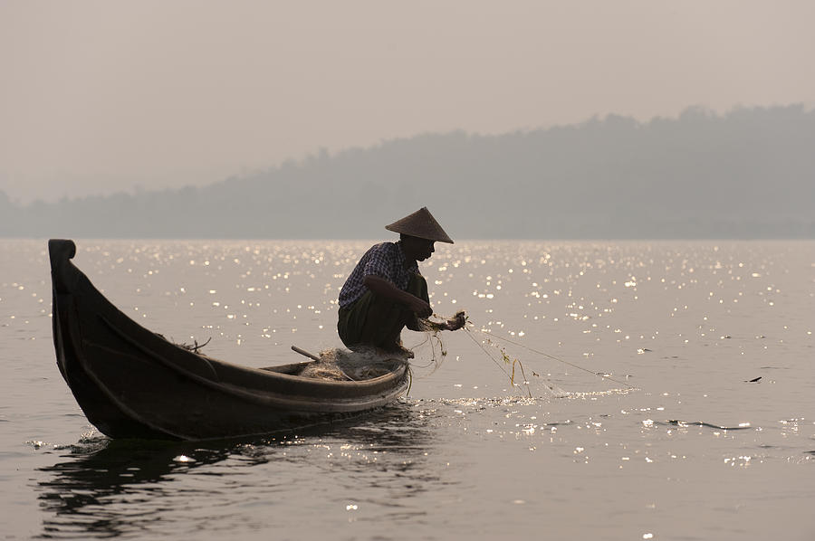 A Fisherman Pulls In His Net Photograph