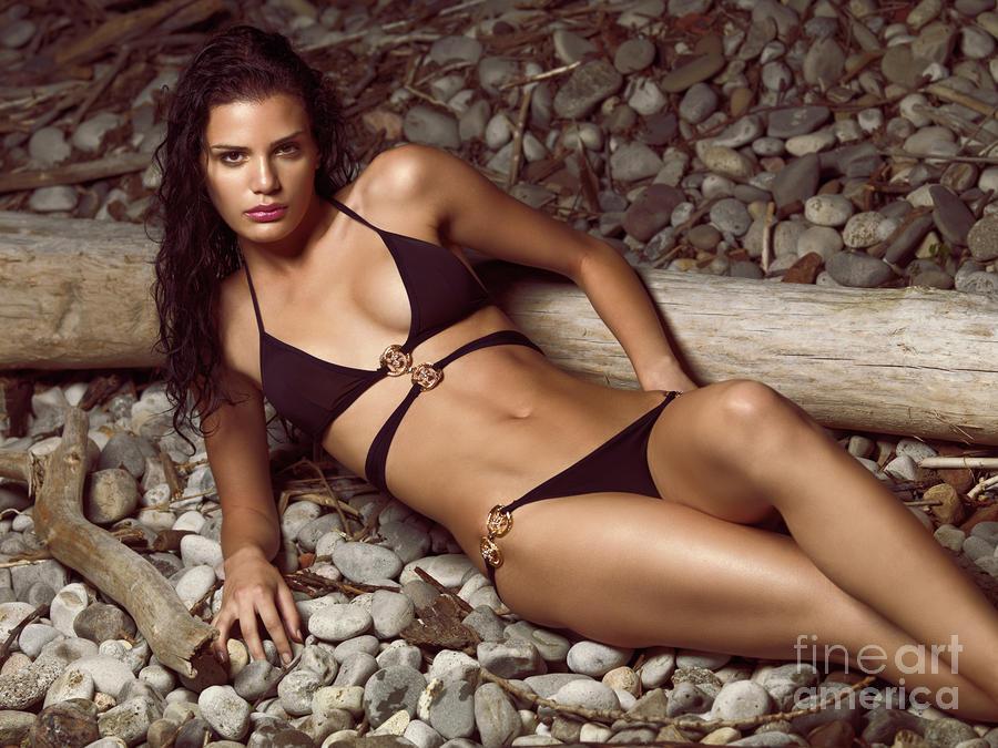 Beautiful Young Woman In Black Bikini On A Pebble Beach Photograph