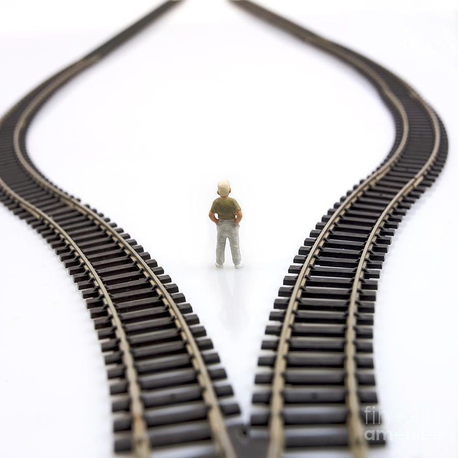 Figurine Between Two Tracks Leading Into Different Directions  Symbolic Image For Making Decisions. Photograph  - Figurine Between Two Tracks Leading Into Different Directions  Symbolic Image For Making Decisions. Fine Art Print