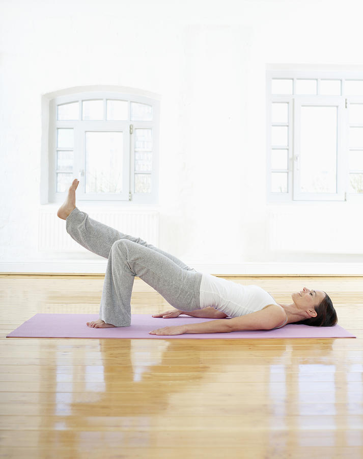 Germany, Hamburg, Woman Doing Yoga Exercise In Gym Room Photograph
