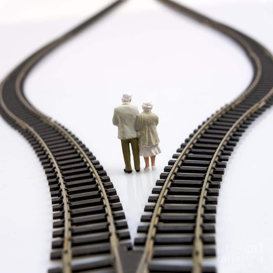 Figurines Between Two Tracks Leading Into Different Directions Symbolic Image For Making Decisions. Photograph