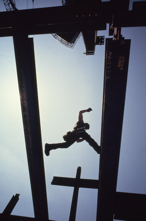A Construction Worker Jumps From Girder Photograph