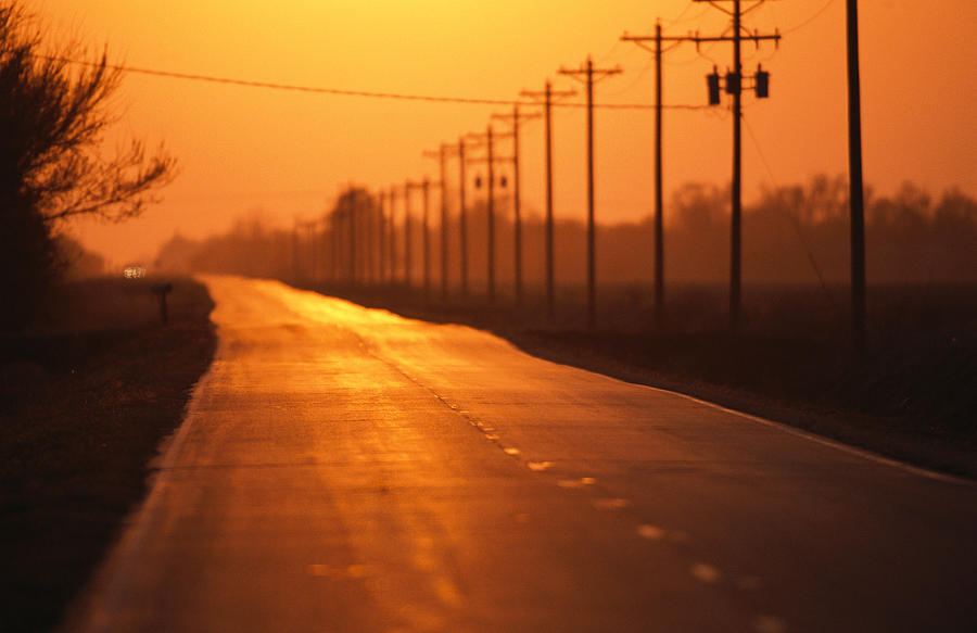 A Country Highway Fades Into The Sunset Photograph