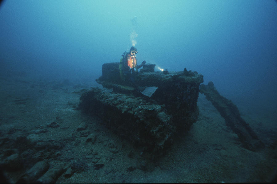 A Diver Inspects A Tractor Dumped Photograph