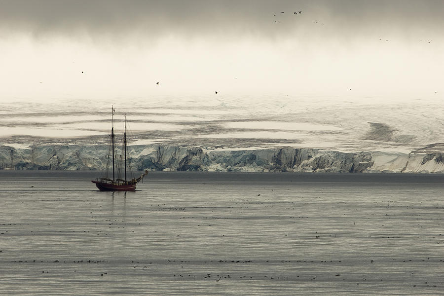 A Double-masted Sailboat Floats Near An Photograph