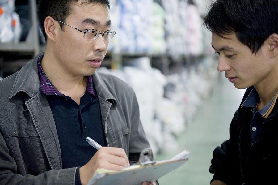 A Factory Employees Discuss Textile Photograph